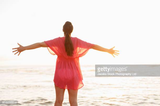 Hispanic woman with arms outstretched on beach