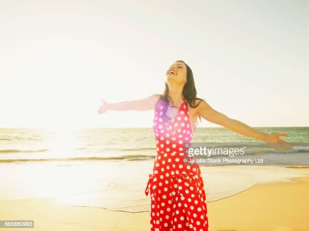 hispanic woman with arms outstretched on beach - plano americano - fotografias e filmes do acervo