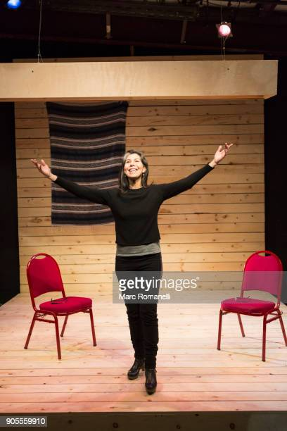Hispanic woman with arms raised on theater stage
