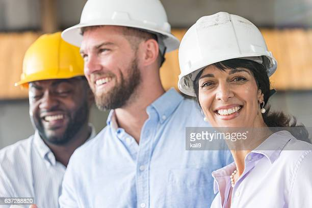 Hispanic woman with group of workers in hardhats