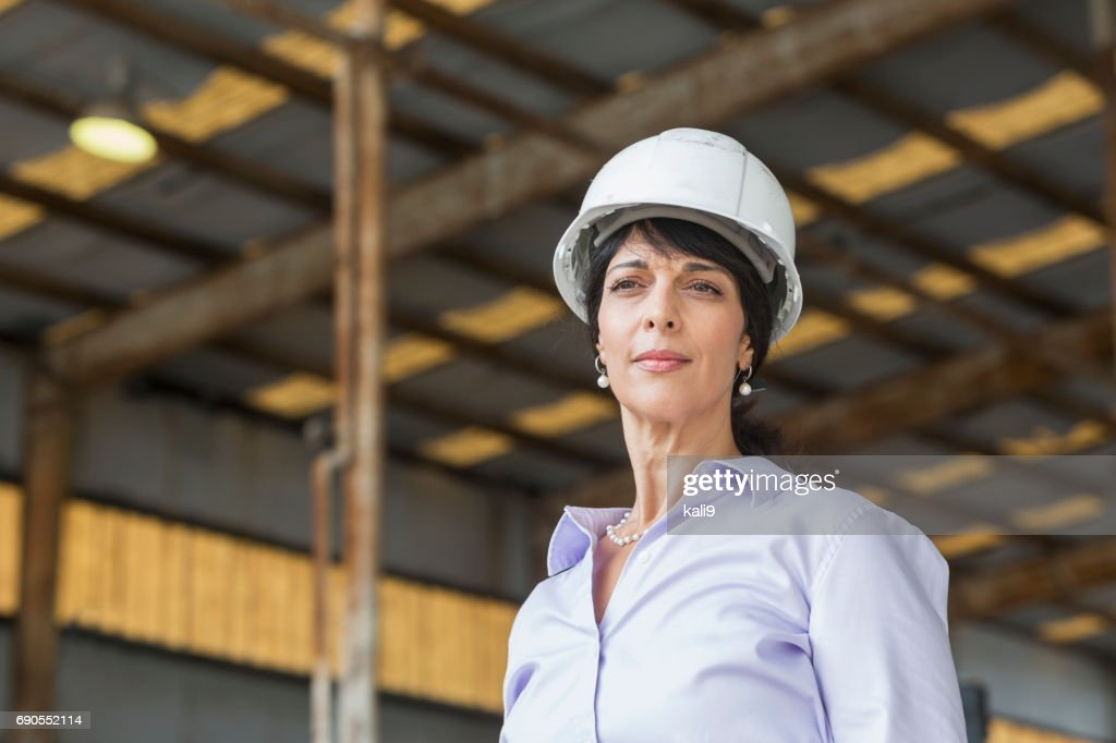 hispanic woman with hardhat working in warehouse stock photo getty