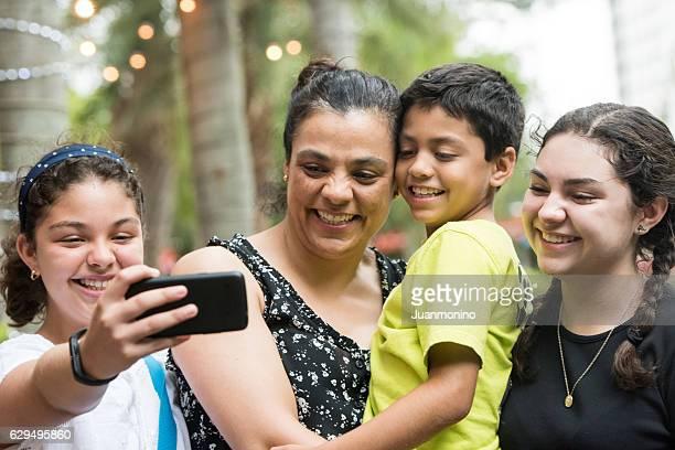 Hispanic Frau mit Ihren Kindern ein selfie