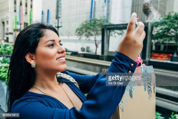 Hispanic woman with shopping bag posing for cell phone selfie