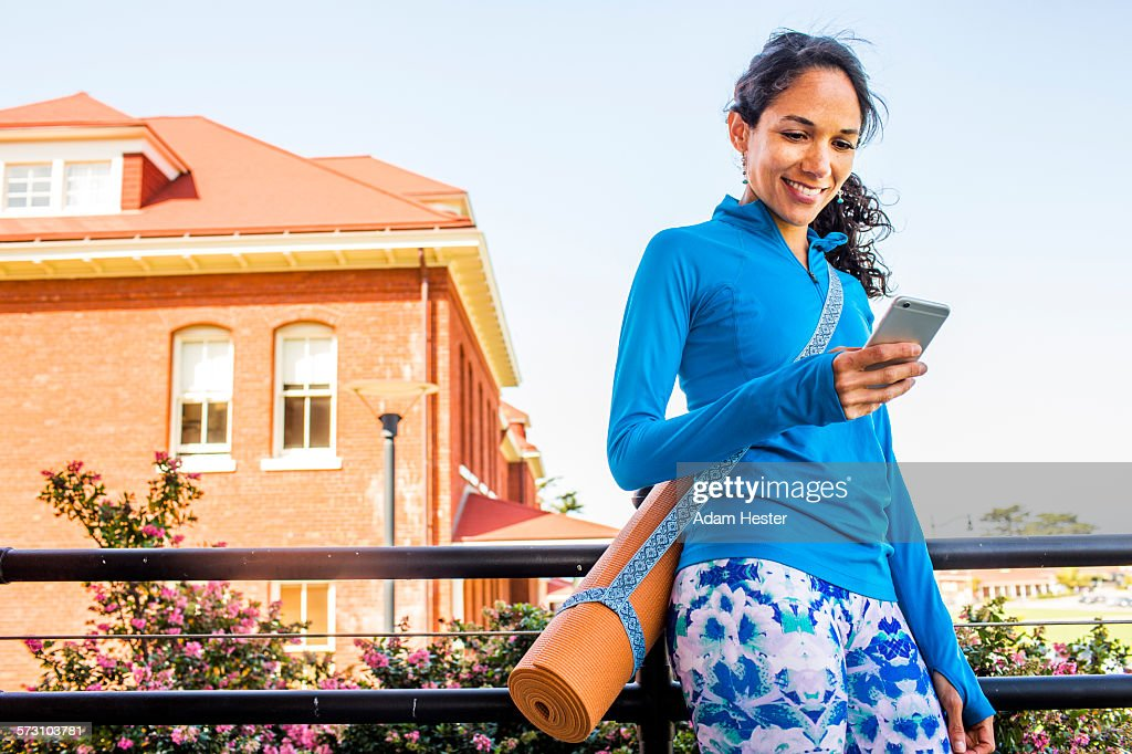Hispanic woman with yoga mat using cell phone : Stock Photo