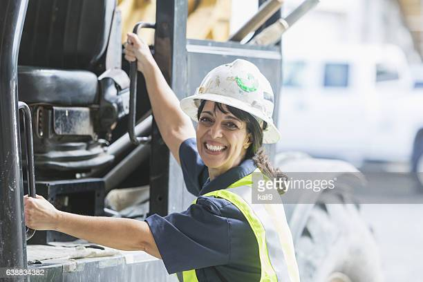 Hispanic woman worker climbing onto forklift