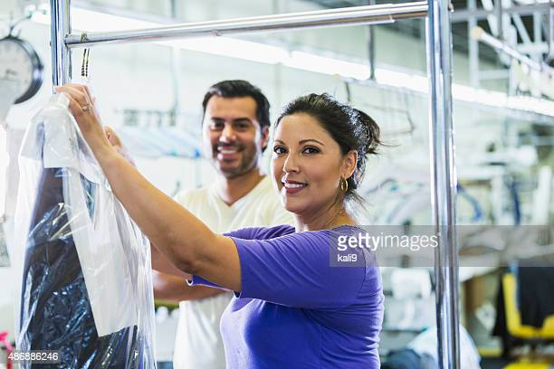 hispanic woman working at a dry cleaner - dry cleaner stock pictures, royalty-free photos & images