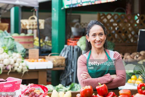 hispanic woman working at fruit and vegetable stand - bancarella di verdura foto e immagini stock
