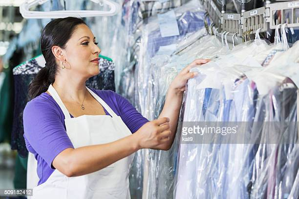 hispanic woman working in dry cleaners - dry cleaner stock pictures, royalty-free photos & images