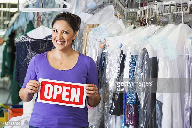 Hispanic woman working in dry cleaners with OPEN sign