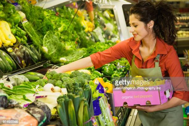 Hispanic woman working in produce section of grocery store