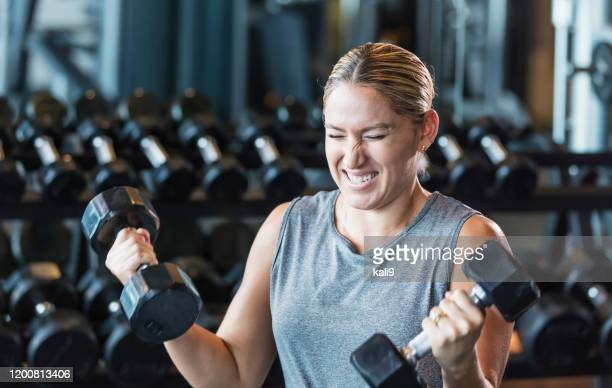 hispanic woman working out at gym, lifting dumbbells - clenching teeth stock pictures, royalty-free photos & images