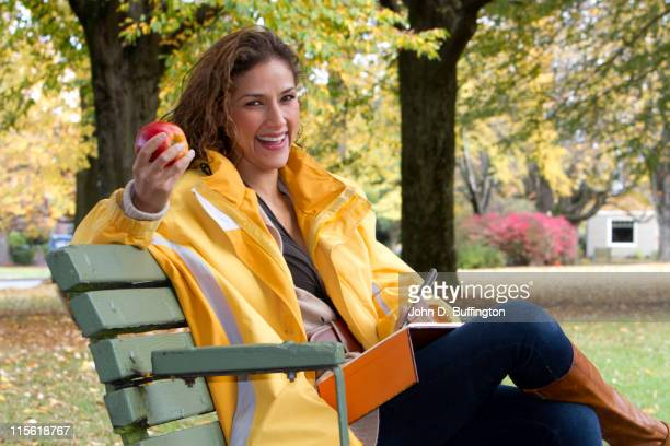 Hispanic woman writing in journal in park