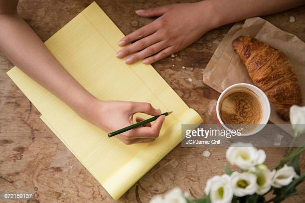 hispanic woman writing on yellow notepad at breakfast - correspondence stock pictures, royalty-free photos & images