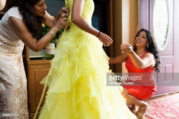 Hispanic women adjusting quinceanera dress in living room