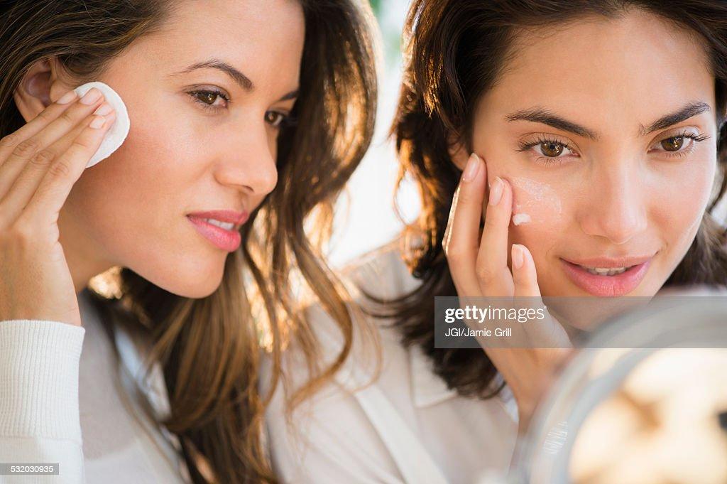 Hispanic women applying makeup in mirror : Stock Photo