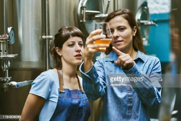 醸造所でクラフトビールの品質をチェックヒスパニックの女性 - 醸造所 ストックフォトと画像
