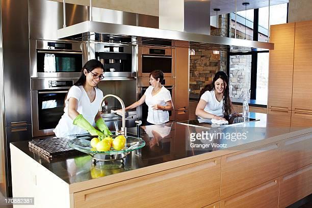 Hispanic women cleaning kitchen