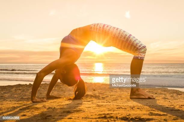 Hispanic Women Doing Yoga On The Ocean