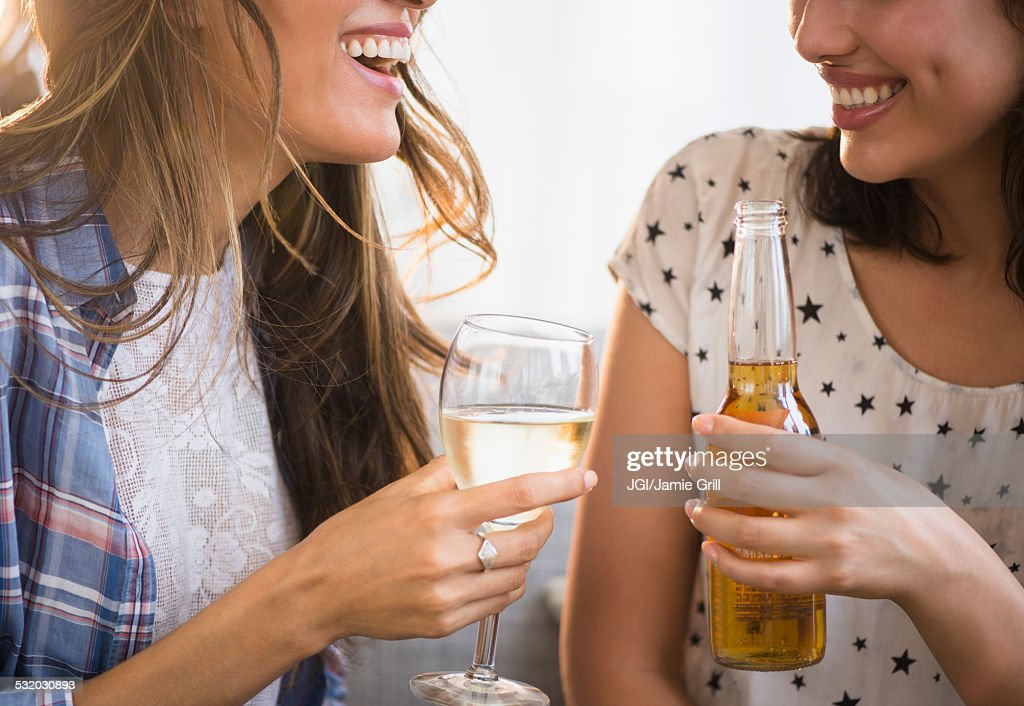 Hispanic women drinking beer and wine together : Stock Photo