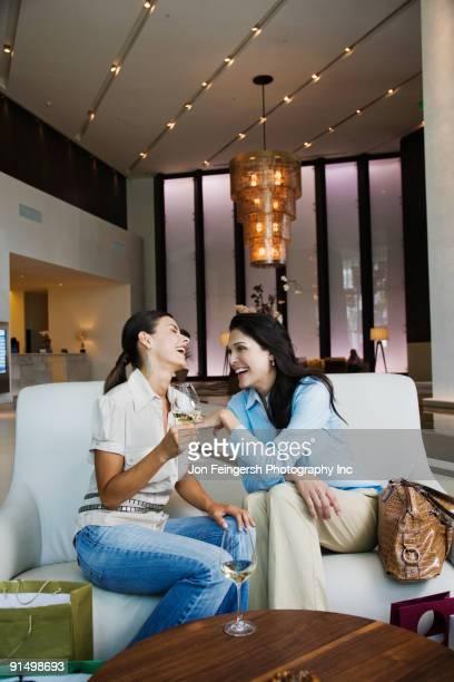 Hispanic women drinking white wine in hotel lobby