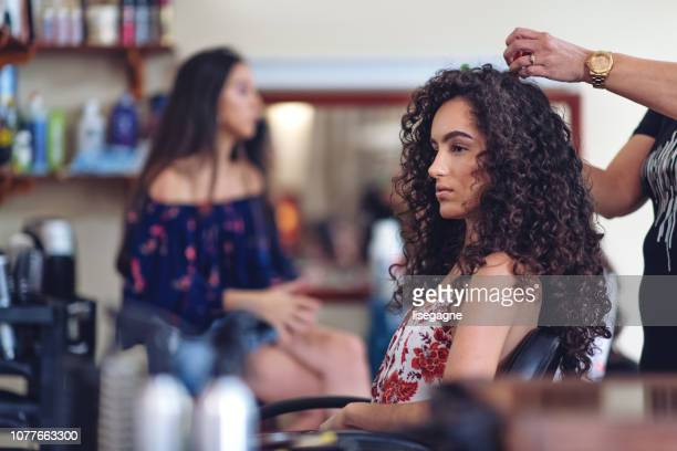 hispanic women in a hair salon - curly stock pictures, royalty-free photos & images