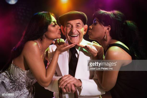 hispanic women kissing senior man in nightclub - may december romance stock photos and pictures