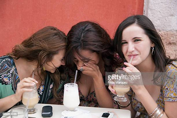 Hispanic women laughing and drinking at cafe