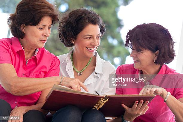 Hispanic women looking at photograph album