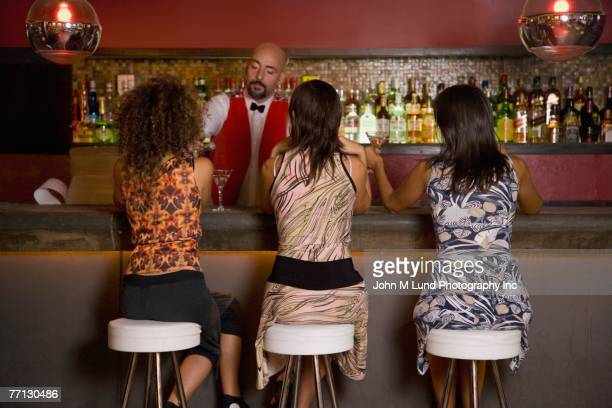 hispanic women sitting at bar - john lund stock pictures, royalty-free photos & images