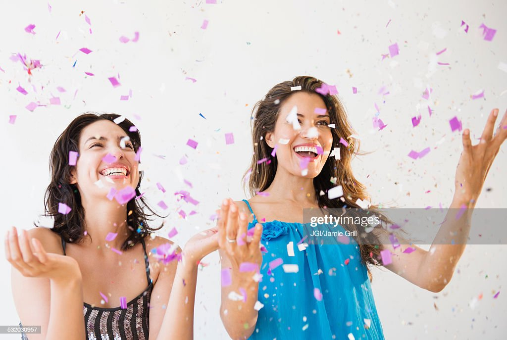 Hispanic women throwing confetti at party : Stock Photo