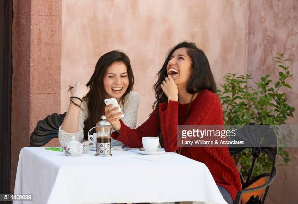 Hispanic women using cell phone at sidewalk cafe