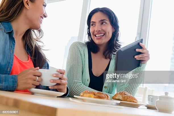 Hispanic women using digital tablet at breakfast