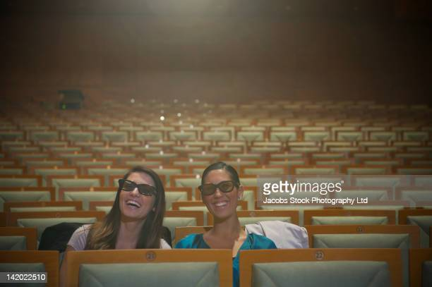Hispanic women watching 3-D movie in theater