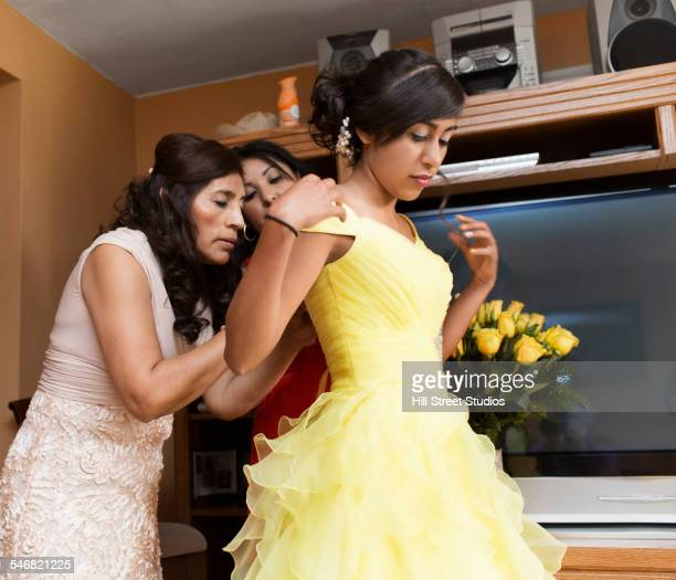 Hispanic women zipping quinceanera dress in living room