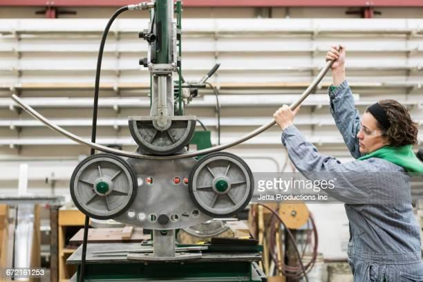 Hispanic worker bending metal rod with machinery