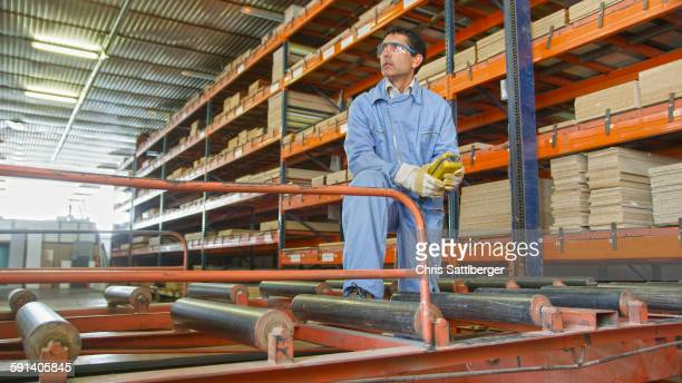 Hispanic worker checking inventory in factory