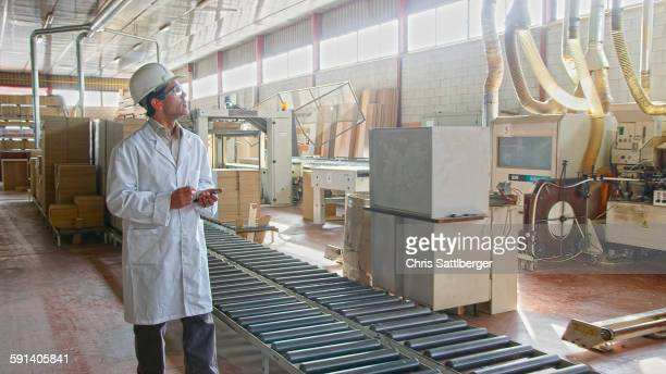 Hispanic worker checking production line in factory