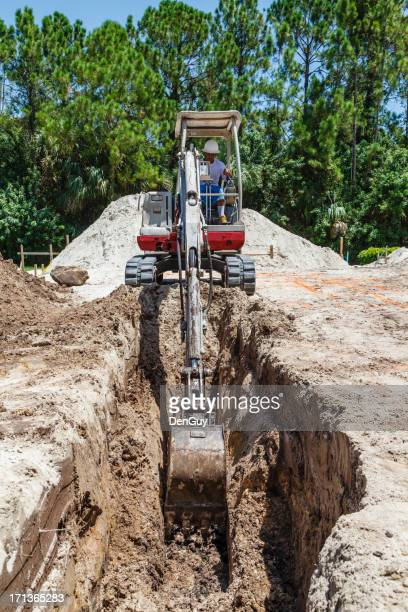 Hispanic Worker Operates Backhoe on Job Site
