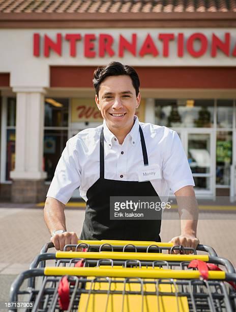 Hispanic worker pushing carts outside grocery store