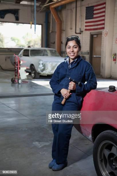 hispanic worker smiling in auto body shop - combinaison de protection photos et images de collection