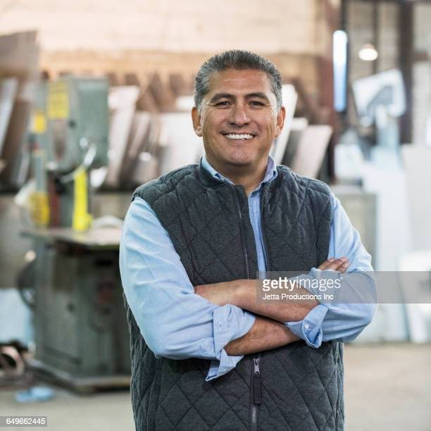 hispanic worker smiling in workshop - jetta productions stock pictures, royalty-free photos & images