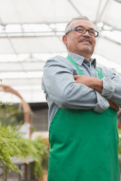 Hispanic worker standing in greenhouse with arms crossed