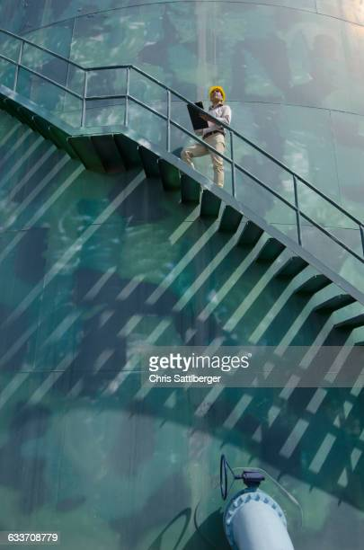 Hispanic worker standing on silo staircase