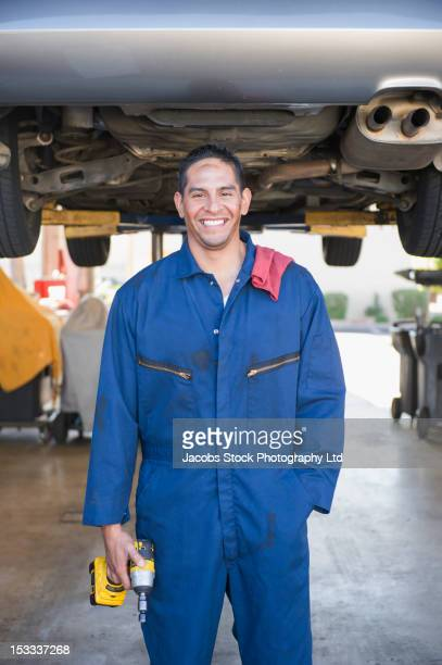Hispanic worker standing underneath car