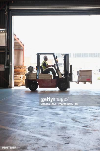 Hispanic worker using forklift in warehouse