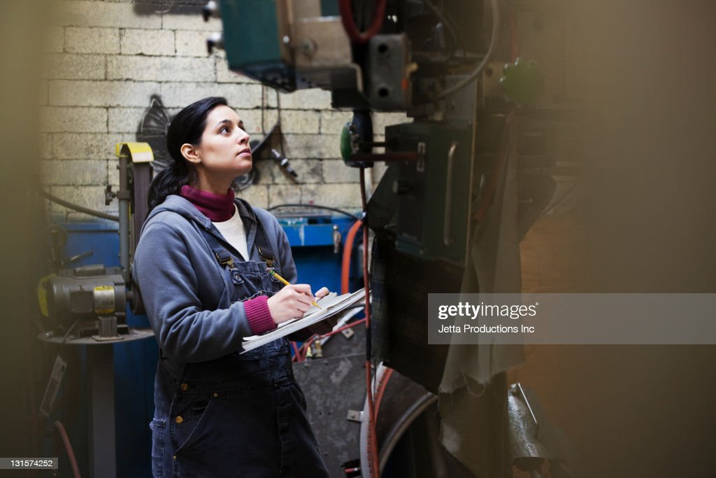 Hispanic worker with clipboard working in factory : Stock Photo