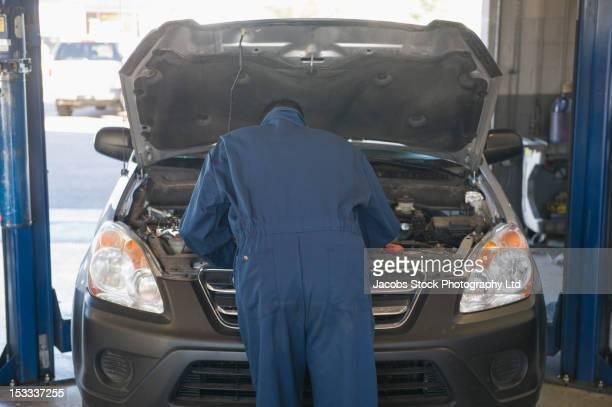 Hispanic worker working on automobile engine