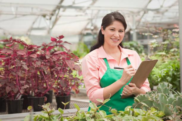 Hispanic worker writing on clipboard in greenhouse