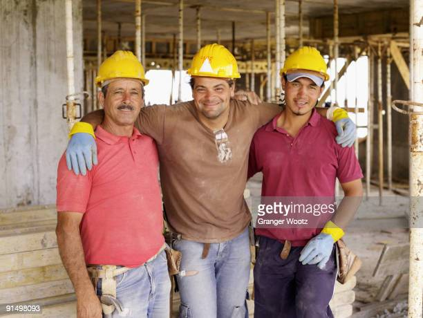 Hispanic workers hugging on construction site