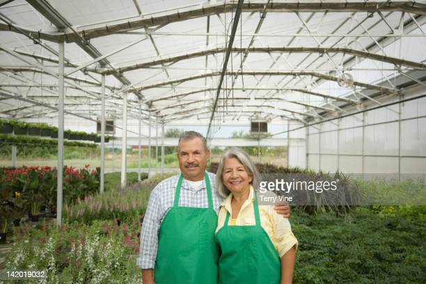 Hispanic workers standing in greenhouse
